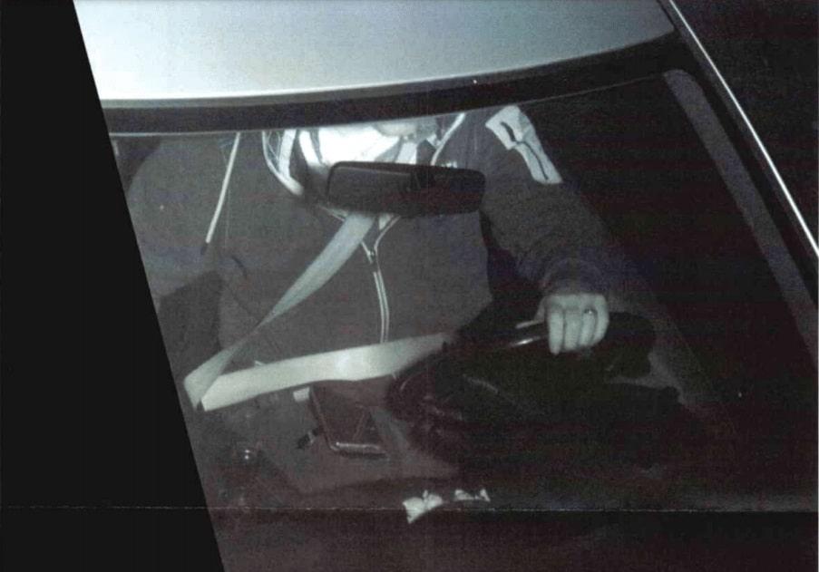 foto van een bestuurder met zijn telefoon op schoot tijdens het rijden